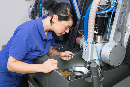 Technician in a dental lab working at a drilling or milling machine