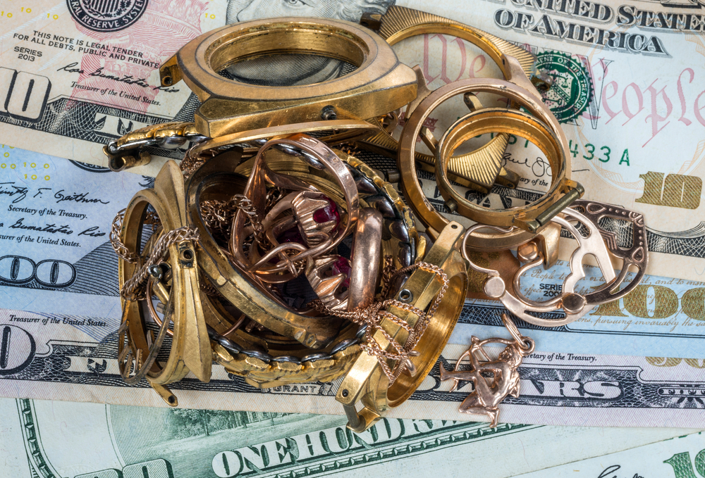 old gold jewelry on dollar bills